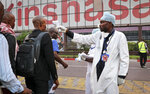 In this photo taken Saturday, June 2, 2018, a health worker checks people's temperatures as they disembark a plane at the airport in Kinshasa, Congo. Hundreds are being vaccinated in Congo's deadly Ebola outbreak but busy taxi drivers who might be ferrying the sick in Mbandaka, an infected city of more than 1 million, argue they are on the front lines as well and should receive the vaccine. (AP Photo/Sam Mednick)