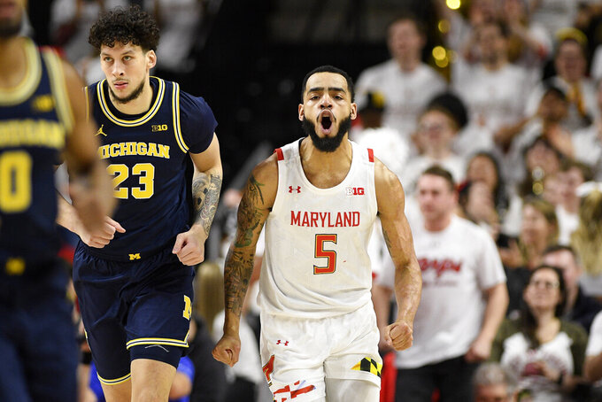 Maryland guard Eric Ayala (5) reacts next to Michigan forward Brandon Johns Jr. (23) during the first half of an NCAA college basketball game, Sunday, March 8, 2020, in College Park, Md. (AP Photo/Nick Wass)