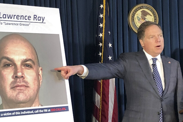 U.S. Attorney Geoffrey Berman points to a photo showing Lawrence Ray during a news conference, Tuesday, Feb. 11, 2020, in New York.  Ray, an ex-convict known for his role in a scandal involving former New York police commissioner Bernard Kerik, was charged Tuesday with federal extortion and sex trafficking charges involving a group of students at Sarah Lawrence College. (AP Photo/Jim Mustian)