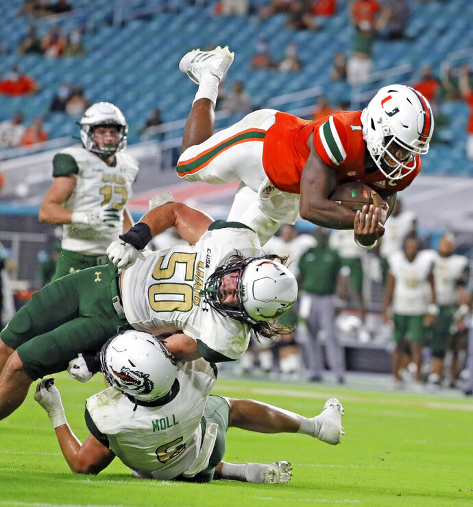 File-Miami quarterback D'Eriq King (1) leaps for a second-quarter touchdown against UAB during an NCAA college football game in Miami Gardens, Fla., Thursday, Sept. 10, 2020. King will lead Miami against Florida State Saturday, Sept. 26, 2020. (Al Diaz/Miami Herald via AP, File)
