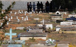 People attend the burial of Jose Mario de Souza Veiga, 83, whose family said died of COVID-19, at the Campo da Esperanca cemetery on the border of the neighborhoods of Taguatinga and Ceilandia, in Brasilia, Brazil, Tuesday, July 21, 2020. (AP Photo/Eraldo Peres)