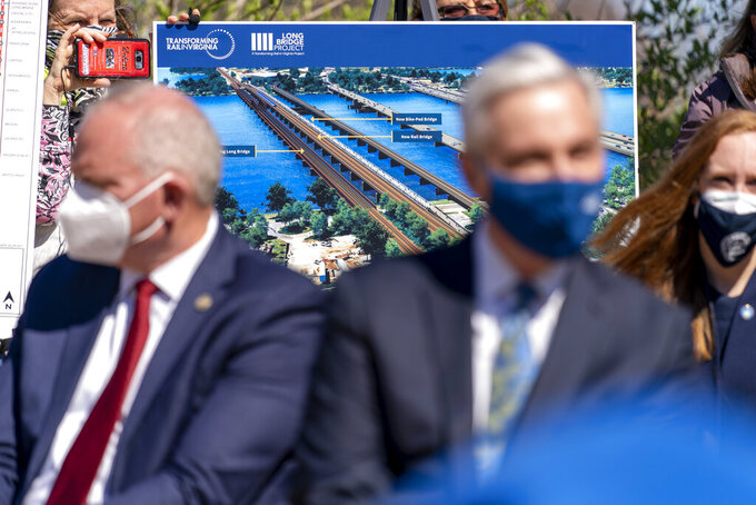 A poster depicting transportation plans are on display behind Amtrak President and CEO William Flynn, center right, and Virginia Railway Express CEO Rich Dalton, left, during a news conference to announce the expansion of commuter rail in Virginia at the Amtrak and Virginia Railway Express (VRE) Alexandria Station, Tuesday, March 30, 2021, in Alexandria, Va. (AP Photo/Andrew Harnik)
