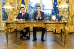FILE - In this photo taken on Dec. 30, 2017 French President Emmanuel Macron delivers a speech next to Spokesperson of the government Benjamin Griveaux at the Elysee Palace in Paris. In a heavy blow to French leader Emmanuel Macron, his former government spokesman pulled out of the race to become mayor of Paris on Friday, after French media reports of leaks onto the internet of compromising sexual images. (Etienne Laurent/ pool via AP, File)