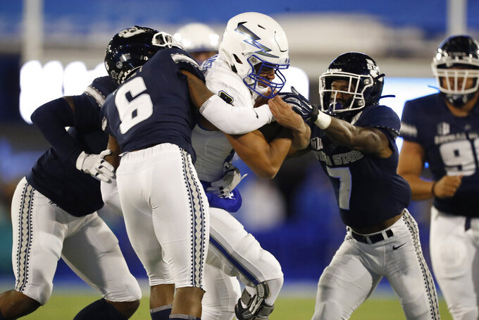 Air Force quarterback Isaiah Sanders, center, is stripped of the ball for a fumble by Utah State cornerback DJ Williams, right, as cornerback Cameron Haney makes the stop after a short gain in the first half of an NCAA college football game Saturday, Oct. 26, 2019, at Air Force Academy, Colo. Utah State recovered the ball. (AP Photo/David Zalubowski)