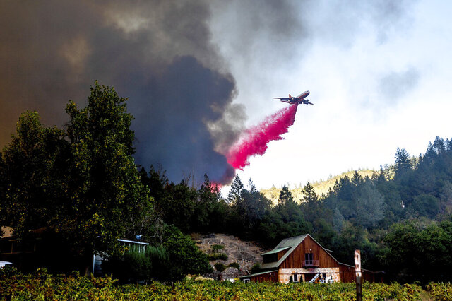 An air tanker drops retardant while battling the Glass Fire in St. Helena, Calif., on Sunday, Sept. 27, 2020. (AP Photo/Noah Berger)