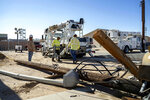In this July 10, 2019 photo provided by the U.S. Navy, civilian workers assigned to Naval Air Weapons Station China Lake repair damaged base infrastructure after multiple earthquakes occurred July 4 and 5 at the base, nearby Ridgecrest and a wide area of Southern California. The base sustained heavy damage that experts estimate will cost over $5 billion to repair. (Mass Communication Specialist 1st Class Arthurgwain L. Marquez/U.S. Navy via AP)