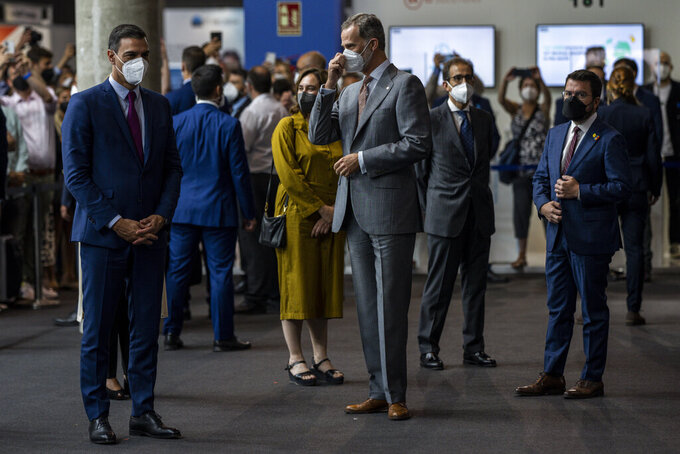 From left to right and foreground, Spanish prime minister Pedro Sanchez, Spain's King Felipe VI and Catalan regional president Pere Aragones visit the Mobile World Congress 2021 venue in Barcelona, Spain, Monday, June, 28, 2021. The Mobile World Congress takes places in Barcelona from June 28 to July 1. (AP Photo/Bernat Armangue)