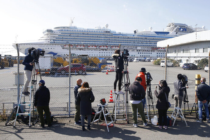 Journalists gather to film the quarantined ship Diamond Princess, background, at Yokohama port in Yokohama, near Tokyo Monday, Feb. 17, 2020. Japanese officials have confirmed 99 more people infected by the new virus aboard the ship, the Health Ministry said Monday. (Mayuko Isobe/Kyodo News via AP)