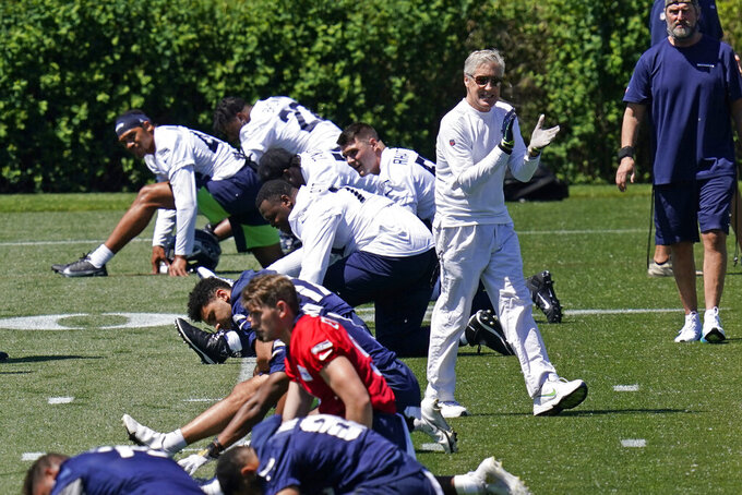 Seattle Seahawks head coach Pete Carroll claps his hands as he walks past players stretching during an NFL football rookie minicamp Friday, May 14, 2021, at the team's training facility in Renton, Wash. (AP Photo/Elaine Thompson)