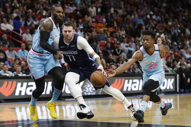 Dallas Mavericks guard Luka Doncic (77) drives to the basket against Miami Heat forwards Jae Crowder, left, and Jimmy Butler (22) during the first half of an NBA basketball game, Friday, Feb. 28, 2020, in Miami. (AP Photo/Wilfredo Lee)