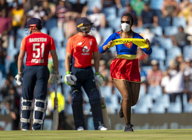 A pitch invader runs past England players during the final T20 cricket match between South Africa and England at Centurion Park in Pretoria, South Africa, Sunday, Feb. 16, 2020. (AP Photo/Themba Hadebe)