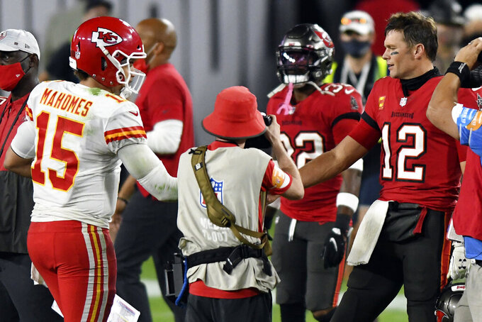 FILE- In this Nov. 29, 2020, file photo, Tampa Bay Buccaneers quarterback Tom Brady (12) congratulates Kansas City Chiefs quarterback Patrick Mahomes (15) after their NFL football game in Tampa, Fla. The Super Bowl matchup features the most accomplished quarterback ever to play the game who is still thriving at age 43 in Brady against the young gun who is rewriting record books at age 25.  (AP Photo/Jason Behnken, File)