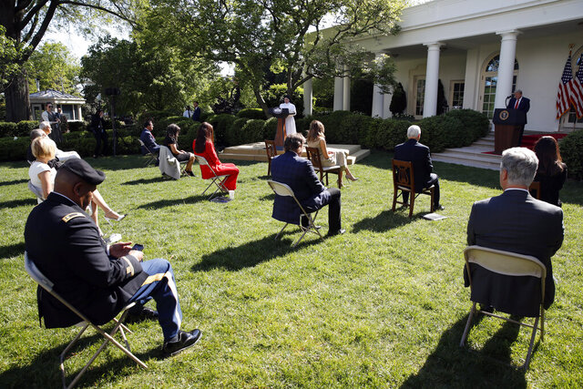 President Donald Trump listens as Sister Eneyda Martinez, with Poor Sisters of St. Joseph, at left podium, speaks during a White House National Day of Prayer Service in the Rose Garden of the White House, Thursday, May 7, 2020, in Washington. (AP Photo/Alex Brandon)