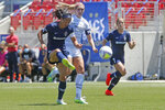 North Carolina Courage defender Abby Erceg, left, kicks the ball as Portland Thorns forward Morgan Weaver, center, looks on during the second half of an NWSL Challenge Cup soccer match at Zions Bank Stadium Saturday, June 27, 2020, in Herriman, Utah. Coach Paul Riley calls Erceg the bedrock of the North Carolina Courage. The New Zealand native is captain of the Courage, the two-time National Women's Soccer League defending champions.(AP Photo/Rick Bowmer)