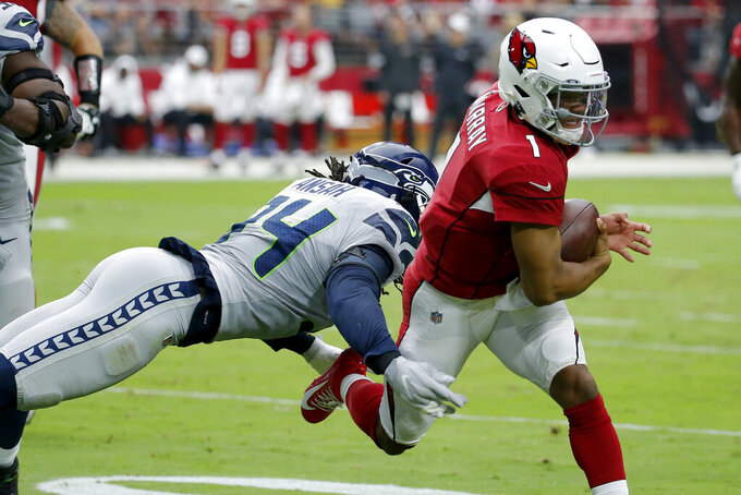 Arizona Cardinals quarterback Kyler Murray (1) eludes the reach of Seattle Seahawks defensive end Ezekiel Ansah (94) during the first half of an NFL football game, Sunday, Sept. 29, 2019, in Glendale, Ariz. (AP Photo/Rick Scuteri)