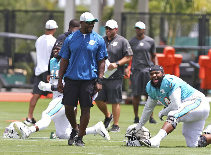 Miami Dolphins head coach Brian Flores talks with defensive tackle Christian Wilkins (94)  during NFL football practice, Wednesday, Sept. 1, 2021 in Miami Gardens, Fla. (David Santiago/Miami Herald via AP)