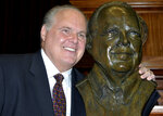 FILE - In this May 14, 2012 file photo, conservative commentator Rush Limbaugh poses with a bust in his likeness during a  ceremony inducting him into the Hall of Famous Missourians in the state Capitol in Jefferson City, Mo. Limbaugh says he's been diagnosed with advanced lung cancer. Addressing listeners on his program Monday, Feb. 3, 2020, he said he will take some days off for further medical tests and to determine treatment. (AP Photo/Julie Smith, File)