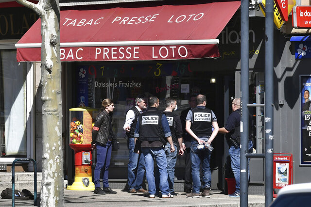 Police officers gather after a man wielding a knife attacked residents venturing out to shop in the town under lockdown, Saturday April 4, 2020 in Romans-sur-Isere, southern France. The alleged attacker was arrested by police nearby, shortly after the attack. Prosecutors did not identify him. They said he had no documents but claimed to be Sudanese and to have been born in 1987. (AP Photo)