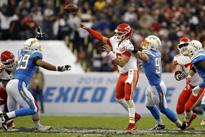 Kansas City Chiefs quarterback Patrick Mahomes throws a pass under pressure from Los Angeles Chargers defensive end Joey Bosa during the second half of an NFL football game Monday, Nov. 18, 2019, in Mexico City. (AP Photo/Marcio Jose Sanchez)