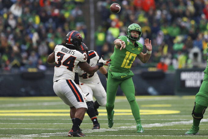 Oregon quarterback Justin Herbert (10) throws a pass away from Oregon State inside linebacker Avery Roberts (34) and defensive lineman Simon Sandberg (45) during the second half of an NCAA college football game in Eugene, Ore., Saturday, Nov. 30, 2019. (AP Photo/Amanda Loman)