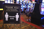 A sign asks people to practice social distancing the Golden Nugget Casino in Atlantic City, N.J., Thursday, July 2, 2020. Eager to hit the slot machines and table games after a 108-day absence, gamblers wore face masks and did without smoking and drinking Thursday as Atlantic City's casinos reopened amid the coronavirus pandemic that has drastically changed things both inside and outside the casino walls. (AP Photo/Seth Wenig)