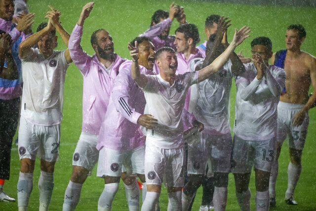 Inter Miami players greet fans in the rain after a win over FC Cincinnati in an MLS soccer match Sunday, Nov. 8, 2020, in Fort Lauderdale, Fla. (David Santiago/Miami Herald via AP)