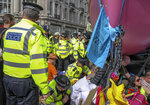 Police talk to protesters as they block traffic on London's Oxford Circus, Thursday, April 18, 2019. The group Extinction Rebellion is calling for a week of civil disobedience against what it says is the failure to tackle the causes of climate change. (AP Photo/Vudi Xhymshiti)