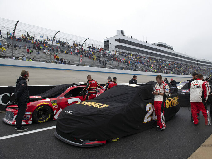 Teams cover their cars after a NASCAR Cup Series auto race was postponed due to inclement weather conditions Sunday, May 5, 2019, at Dover International Speedway in Dover, Del. (AP Photo/Jason Minto)