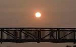 A person crosses a bridge against a hazy sunset over Century Park in Vernon Hills, Ill,, Tuesday, Sept. 15, 2020. The smoke from dozens of wildfires in the western United States has now blanket much of the county along with parts of Mexico and Canada, as residents thousands of miles away on the East Coast are being treated to unusually hazy skies and remarkable sunsets.  (John Starks/Daily Herald via AP)