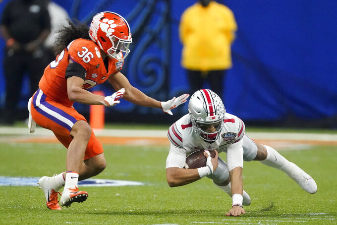Ohio State quarterback Justin Fields is tackled by Clemson safety Lannden Zanders during the first half of the Sugar Bowl NCAA college football game Friday, Jan. 1, 2021, in New Orleans. (AP Photo/John Bazemore)