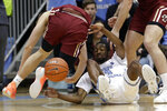 North Carolina guard Brandon Robinson, center, falls to the floor chasing the ball with Boston College guard Julian Rishwain, left, during the first half of an NCAA college basketball game in Chapel Hill, N.C., Saturday, Feb. 1, 2020. (AP Photo/Gerry Broome)