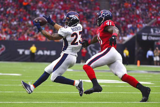 Denver Broncos running back Devontae Booker (23) makes a catch in front of Houston Texans inside linebacker Zach Cunningham (41) during the first half of an NFL football game Sunday, Dec. 8, 2019, in Houston. (AP Photo/Eric Christian Smith)