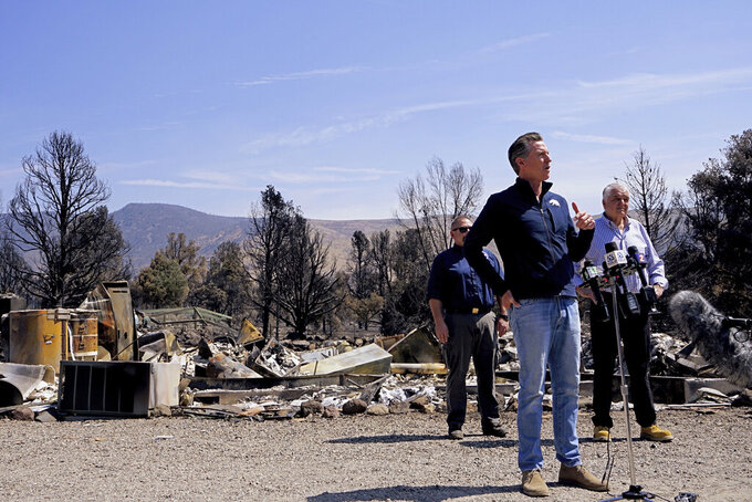 California Gov. Gavin Newsom, left, and Nevada Gov. Steve Sisolak speak after touring homes destroyed by wildfires near where the Tamarack Fire ignited earlier in July in Gardnerville, Nev., Wednesday, July 28, 2021. Nevada Gov. Steve Sisolak and California Gov. Gavin Newsom stood on ashen ground as they surveyed burned homes and a mountain range of pine trees charred by the Tamarack Fire south of Gardnerville, Nevada, near Topaz Lake. The governors, both Democrats, called on the federal government to provide more firefighting resources and stressed that climate change could make wildfires even more intense and destructive in the future. (AP Photo/Sam Metz)