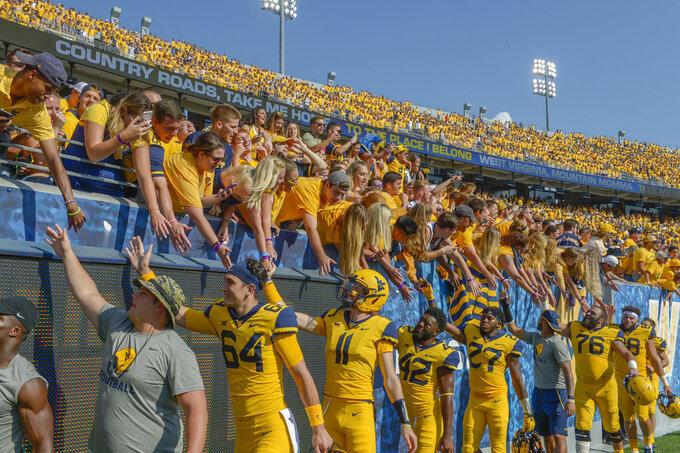 West Virginia lineplayers high-five fans after defeating Kansas 38-22 in an NCAA college football game against Kansas in Morgantown, W. Va., Saturday Oct. 6, 2018. (Craig Hudson/Charleston Gazette-Mail via AP)