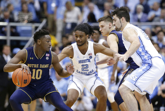 Notre Dame's TJ Gibbs (10) dribbles the ball while North Carolina's Coby White (2) and Luke Maye, right, defend during the first half of an NCAA college basketball game in Chapel Hill, N.C., Tuesday, Jan. 15, 2019. (AP Photo/Gerry Broome)