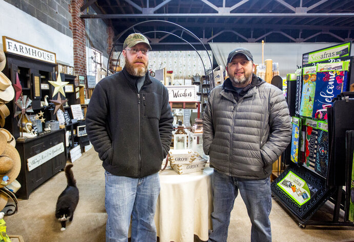 In this Jan. 31, 2020 photo, Blue Ribbon Nursery co-owners Josh Shifflett, left, and Chad Comer pose for a photo in the seasonal area of their store in Broadway, Va. (Daniel Lin/Daily News-Record via AP)