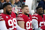 San Francisco 49ers defensive tackle DeForest Buckner (99) smiles as he rests on the bench with defensive end Nick Bosa (97) and defensive end Dee Ford (55) during the second half of an NFL divisional playoff football game against the Minnesota Vikings, Saturday, Jan. 11, 2020, in Santa Clara, Calif. (AP Photo/Tony Avelar)
