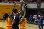 Oklahoma State's Isaac Likekele (13) and Matthew-Alexander Moncrieffe (12) guard Texas Christian center Kevin Samuel (21) during the first half of the NCAA college basketball game in Stillwater, Okla., Wednesday, Dec. 16, 2020. (AP Photo/Mitch Alcala)