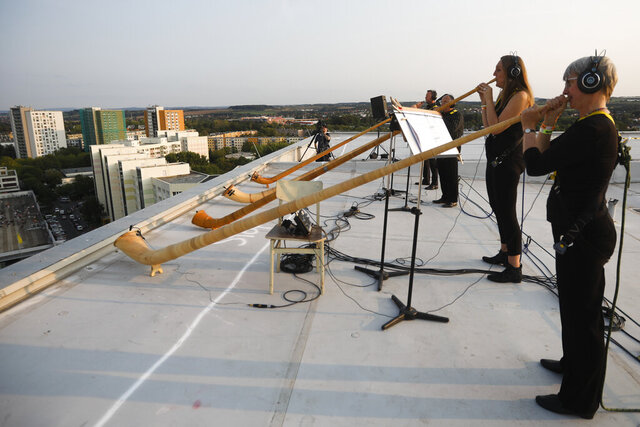 A musician with alp horns perform on the roof of an apartment block for a concert featuring distant harmonies, at a time when cultural events have been disrupted by the coronavirus pandemic, in the Prohlis neighborhood in Dresden, Germany, Saturday, Sept. 12, 2020. About 33 musicians of the Dresden Sinfoniker perform a concert named the 'Himmel ueber Prohils', The Sky above Prohlis, on the roof-tops of communist-era apartment blocs in the Dresden neighborhood Prohlis. (AP Photo/Markus Schreiber)