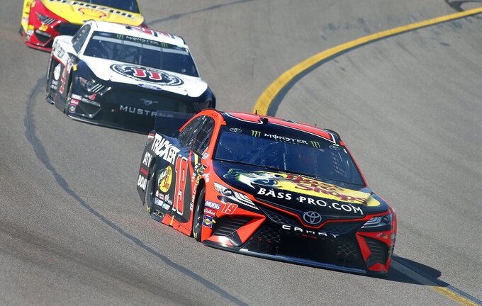 Martin Truex Jr. (19) drives out of Turn 4 ahead of Kevin Harvick (4) during a NASCAR Cup Series auto race at ISM Raceway, Sunday, March 10, 2019, in Avondale, Ariz. (AP Photo/Ralph Freso)
