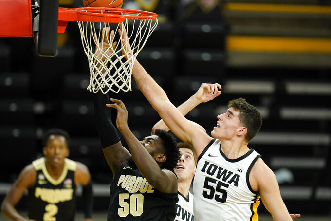 Purdue forward Trevion Williams (50) drives to the basket ahead of Iowa center Luka Garza (55) during the first half of an NCAA college basketball game, Tuesday, Dec. 22, 2020, in Iowa City, Iowa. (AP Photo/Charlie Neibergall)
