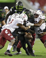 South Florida quarterback Jordan McCloud (12) fumbles the football when he is sandwiched between Temple linebacker Chapelle Russell (3) and defensive tackle Khris Banks (56) during the first half of an NCAA college football game Thursday, Nov. 7, 2019, in Tampa, Fla. Temple recovered the fumble. (AP Photo/Chris O'Meara)
