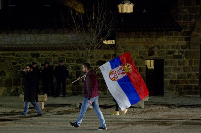 A Kosovo Serb protester carries a Serb flag and joins a demonstration against Serbian President Aleksandar Vucic in the town of Gracanica, Kosovo on Saturday, Feb. 9, 2019. Every Saturday thousands of opponents of Serbian president Aleksandar Vucic march in various cities and towns across Serbia. (AP Photo/Visar Kryeziu)