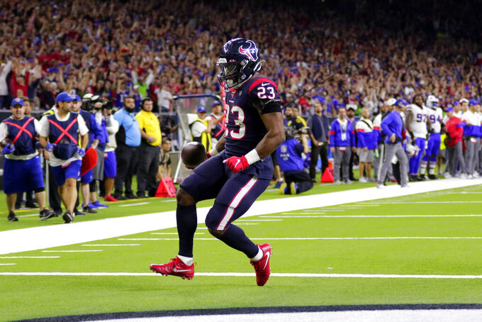 Houston Texans running back Carlos Hyde (23) scores a touchdown after catching a pass against the Buffalo Bills during the second half of an NFL wild-card playoff football game Saturday, Jan. 4, 2020, in Houston. (AP Photo/Michael Wyke)