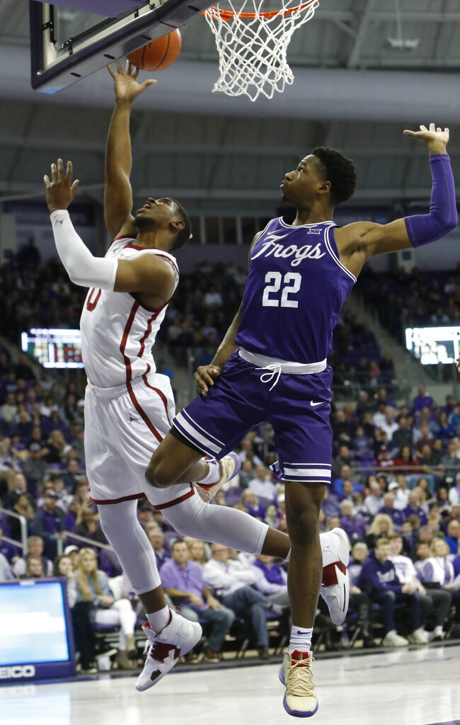 Oklahoma guard Christian James (0) shoots against TCU guard RJ Nembhard (22) during the first half of an NCAA college basketball game in Fort Worth, Texas, Saturday, Feb. 16, 2019. (AP Photo/LM Otero)