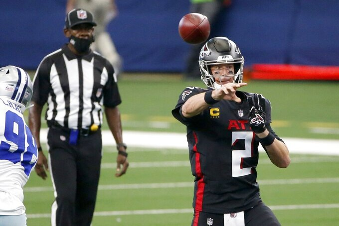 Dallas Cowboys defensive tackle Tyrone Crawford, left, pressures as Atlanta Falcons' Matt Ryan (2) throws a pass in the first half of an NFL football game in Arlington, Texas, Sunday, Sept. 20, 2020. (AP Photo/Ron Jenkins)