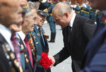 Russian President Vladimir Putin greets WWII veterans during an opening ceremony of the monument to World War II Red Army, in the village of Khoroshevo, just outside Rzhev, about 200 kilometers (about 125 miles) northwest of Moscow, Russia, Tuesday, June 30, 2020. (Mikhail Klimentyev, Sputnik, Kremlin Pool Photo via AP)