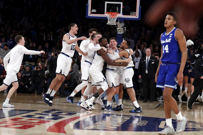 Seton Hall guard Jared Rhoden (14) walks off the court as Villanova players celebrate after winning 74-72 in an NCAA college basketball game in the championship of the Big East Conference tournament, Saturday, March 16, 2019, in New York. (AP Photo/Julio Cortez)
