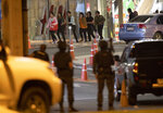 People who were able to get out of Terminal 21 Korat mall walk outside the building in Nakhon Ratchasima, Thailand on Sunday, Feb. 9, 2020. A soldier who holed up in a popular shopping mall in northeastern Thailand shot multiple people on Saturday, killing at least 20 and injuring 31 others, officials said. (AP Photo/Sakchai Lalitkanjanakul)