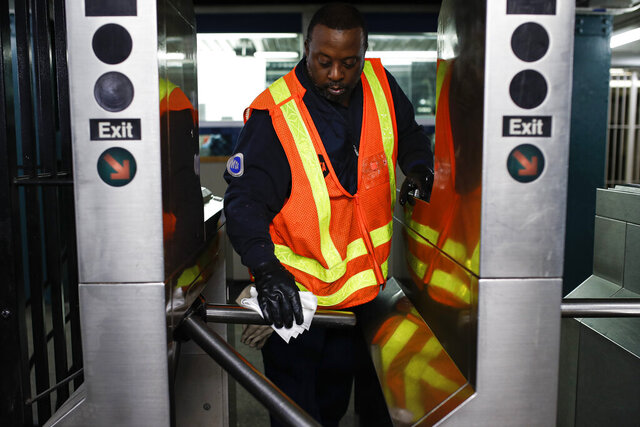 An MTA employee sanitizes surfaces at the CLasson Ave. and Lafayette Ave. subway station with bleach solutions due to COVID-19 concerns, Friday, March 20, 2020, in the Brooklyn Borough in New York. New York Gov. Andrew Cuomo is ordering all workers in non-essential businesses to stay home and banning gatherings statewide.